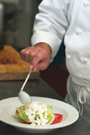Chef preparing a meal on a large white plate